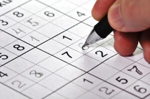 Close-up a pencil in hand and puzzle Sudoku.